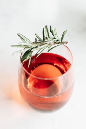 Rosé - Glass of Rosé Water garnished with rosemary.